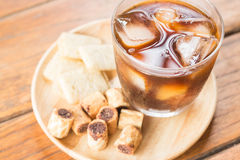 Glass of black iced coffee with some snack. Stock photo Royalty Free Stock Photos