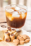 Glass of black iced coffee with some snack Stock Images