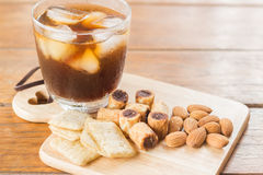 Glass of black iced coffee with some snack Stock Photography