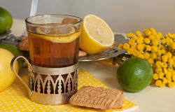 A glass of black tea in a glass holder, some biscuits, ripe lemons and limes on a linen surface against the light background Stock Photo