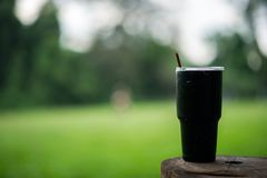A glass of black water is placed on a wooden pole with a plug, t royalty free stock photos