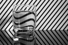 A glass with black and white stripe. A glass of water with black and white stripe background. The reflection of the stripe is on the water stock image