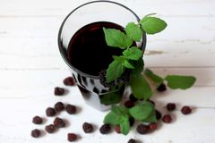 Glass of blackberry juice and mint. Transparent glass of blackberry juice with a sprig of mint royalty free stock photos