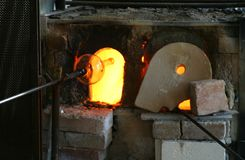 Glass Blast Furnace. Blast furnace for heating glass. This also shows a glass vase being put back in to get reheated before blowing royalty free stock photography