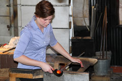 Glass Blower. Woman shaping hot glass in a glass blowing studio in Stockholm Stock Photos