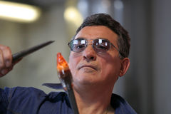 Glass blower. Forming a piece of decorative glass during a demonstration in Murano, Italy stock photography
