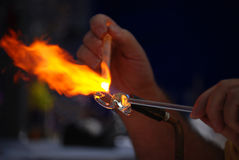 Glass blower creates a swan. The art of glass blowing as an artist creates a swan during a street fest in October Royalty Free Stock Images