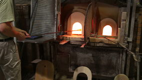 Glass blower master is heating and decorating glass in an oven at glassware factory stock video footage