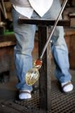 Glass blower shaping molten glass Stock Image