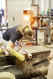 Glass blower. Woman shaping glass vase in traditional glass making studio stock images