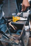 Glass blowing craft shop. Worker`s hands with tools image. Masterpiece creation moment stock photo