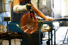 Glass blowing - shaping a vase. Traditional Swedish glass blowing. A hot glowing vase is rolled on its blowing shaft, while a glassblower shapes it Royalty Free Stock Photos