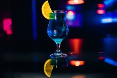 Glass of blue alcohol cocktail Martini with a slice of orange party at bar Royalty Free Stock Photography