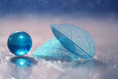 A glass blue ball and a transparent leaf skeleton on a glass table with reflection and a beautiful bokeh. Royalty Free Stock Images
