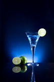 A glass of blue cocktail with green lime on the bar with  dark t Stock Image