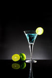 A glass of blue cocktail with green lime on the bar with dark to. Ne background Stock Image