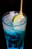 Glass of blue cocktail with lime on black Stock Photo