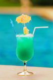 Glass of blue cocktail at swimming pool in summer time Royalty Free Stock Photos