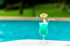 Glass of blue cocktail at swimming pool in summer time Stock Image