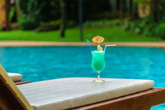 Glass of blue cocktail at swimming pool in summer time Royalty Free Stock Photography