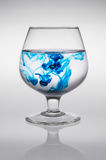 Glass with blue ink that creates waves of color creating of colored waves. Glass with blue ink that creates waves of color Royalty Free Stock Image