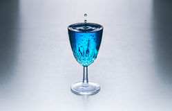 Glass with blue water on a table Stock Photo