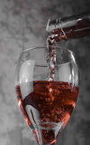 Glass of blush. Blush wine being poured into a tall white wine glass Stock Images