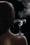 Glass of boiling water on the shoulder of the girl Stock Images
