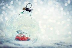 Glass boll för jul i snö med miniatyrvintervärlden inom arkivbild