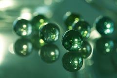 Glass bollar på en glass tabell med en reflexion av gräsplan Sju glass bollar Selektivt fokusera Royaltyfria Bilder