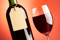Glass and bottle. Of red wine with blank tag Royalty Free Stock Photo