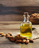 Glass bottle with almond oil. Bottle with almond oil on wooden background Stock Photo