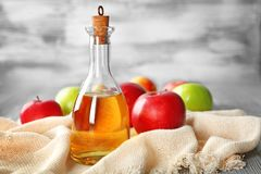 Glass bottle with apple vinegar. And fresh fruit on table royalty free stock photo