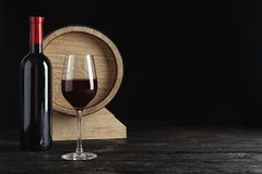 Glass, bottle and barrel with delicious red wine. On table against dark background Stock Photography