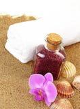 Glass bottle with  bath salt on beach background Stock Photography