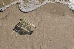Glass bottle on the beach. Glass bottle with shade from the sun on the beach Royalty Free Stock Photos