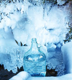 Glass bottle with beautiful frozen winter spring. Blue color background. Stock Images