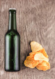 Glass bottle of beer and chips Royalty Free Stock Images