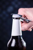 Glass bottle of beer and opener on a dark background. Hand opening a bottle. Alcohol and drinks concept. Royalty Free Stock Images