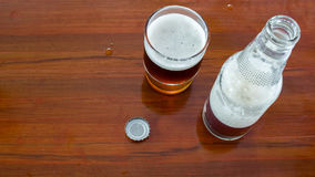 Glass and bottle of beer with openned bottle cap on wooden table Royalty Free Stock Images