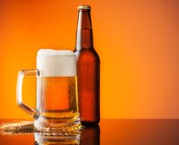 Glass and bottle of beer with orange background Royalty Free Stock Photography
