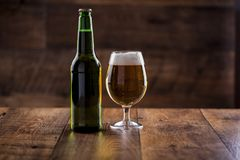 A glass and a bottle of beer. Session with a glass of beer and a closet in macro close-ups royalty free stock photography