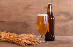 Glass and bottle of beer with wheat ears on wooden Royalty Free Stock Images