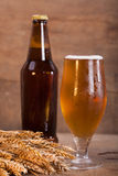 Glass and bottle of beer with wheat ears on wooden Stock Photo