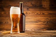 Glass and bottle of beer on wooden planks Royalty Free Stock Images