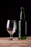 Glass and bottle with beer on wooden table Royalty Free Stock Images