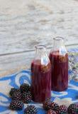 Glass bottle of blackberries juice. Closeup Royalty Free Stock Photo