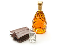 Glass bottle of brandy wallet and small glass Royalty Free Stock Photo