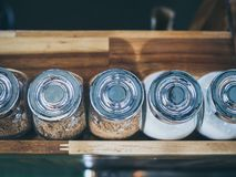 Glass bottle of brown sugar and white sugar on wooden shelf in cafe top view stock image