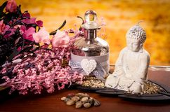 Glass bottle and buddha statue with flowers spa Stock Photos